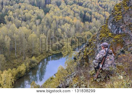 Hunter with a gun in the mountains watching the forest
