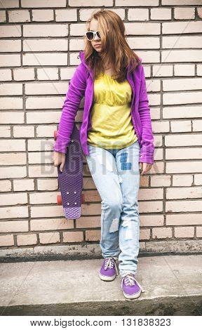 Girl In Colorful Clothes With A Skateboard