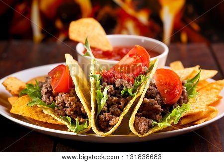plate with taco nachos chips and tomato dip