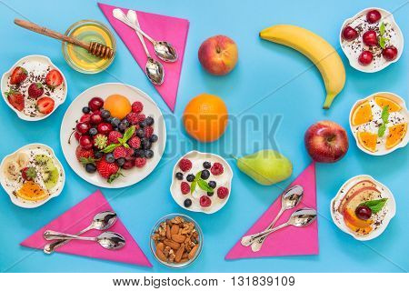 6 bowls of yogurt dressed with different ingredients fruit berries nuts honey and 6 spoons napkins and right up some empty space on light blue background. Horizontal. Top view.