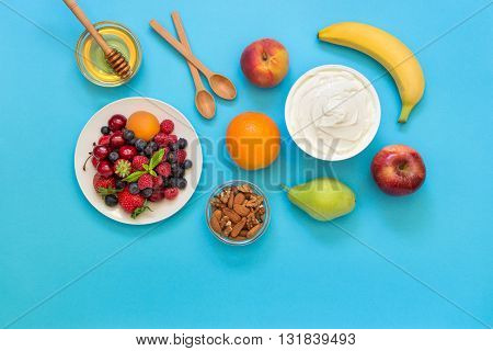 Greek yogurt around fruits orange banana pear peach apple plate with strawberries raspberries blueberries and nuts honey and 2 wooden spoons on light blue background. Horizontal. Top view.