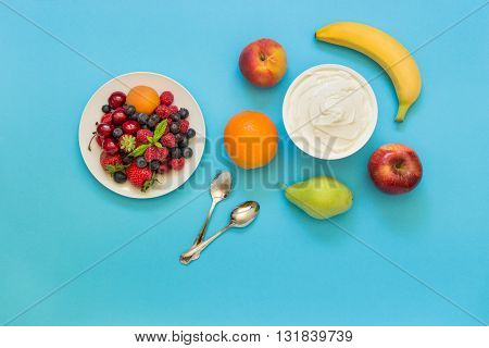 Greek yogurt around orange banana pear peach apple plate with strawberries raspberries blueberries and two spoons on light blue background. Horizontal. Top view.