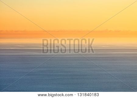 Orange sunset over the blue sea in pastel colors