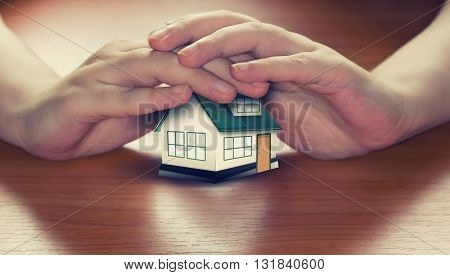 Hands saving small house on a wooden surface