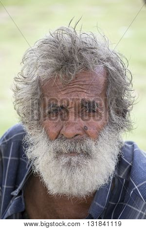 MATARA SRI LANKA - NOVEMBER 5 2014: Unidentified old Sri Lankan beggar waits for alms on a street next to the bus station