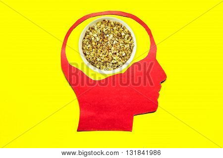 Oatmeal porridge close up in red paper human head on yellow background