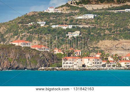 Rocky coastline along Caribbean Sea with mountain-side resorts and villa's