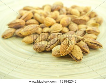 Group of organic almonds on wooden plate