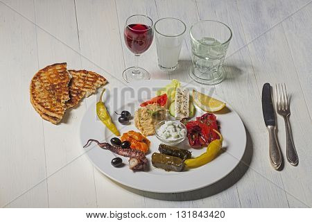 variety of greek appetizers with wine and ouzo