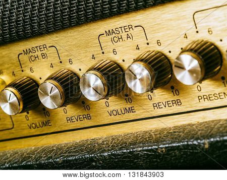 Macro photo of a vintage electric guitar amplifier focusing on the volume knob which is set at ten.