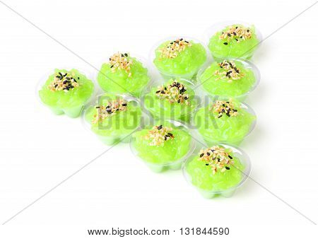 Triangle of pandan flavored sweet translucent gelatinous rice on white floor.