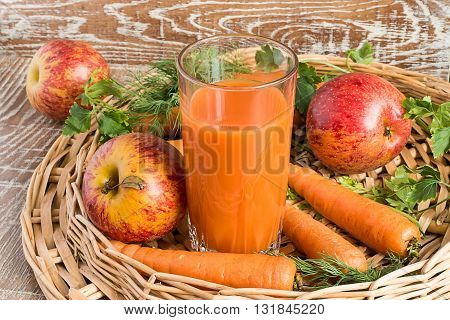 A glass with juice, fresh apples and carrots in a wicker basket on a brown wooden background.