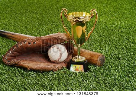 closeup baseball trophy with bat ball and glove on grass