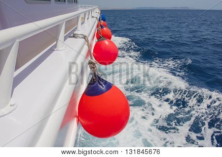 View down the side of a private motor yacht traveling on tropical ocean with fenders
