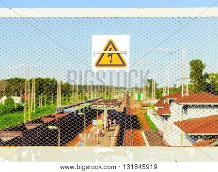 High voltage sign at railway station in sunny day