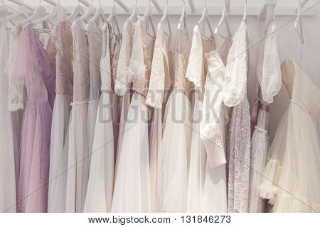 Wide section of wedding dress hanging on rack in a shop