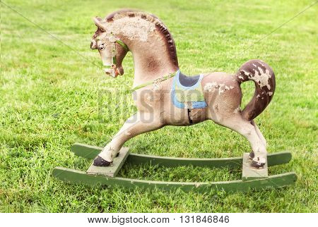 Nice vintage rocking horse at green summer grass