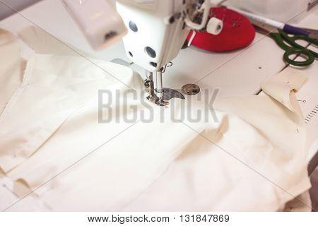 Close up of sewing-machine making wedding dress