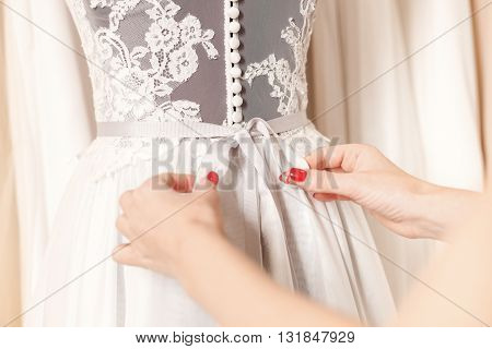 Close up of female hands adjusting bow on back of wedding clothing