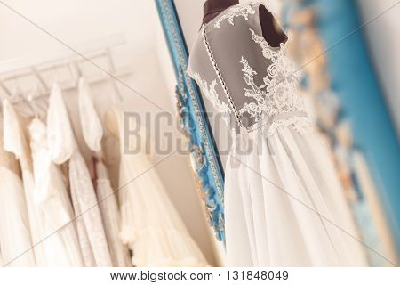 Beautiful wedding dress on mannequin in atelier. Various bridal clothing in hanging on background