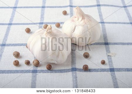 Garlic With Black Bell Pepper On Squared Print Cloth Table