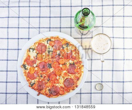 Hot Delicious Pizza With Glass Of Beer On Squared Cloth
