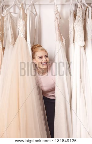Beautiful young woman is standing between elegant wedding dresses. She is peeping through clothing and smiling with joy