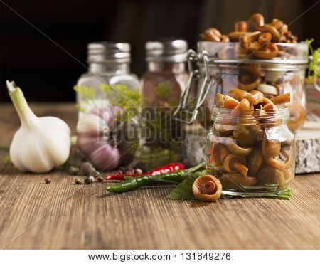 Saffron milk cap mushrooms pickled garlic dill and pepper in a bowl and banks in a simple wooden background. Rustic style. selective Focus
