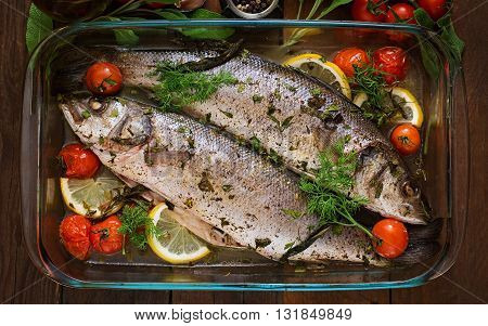 Two Baked Seabass In A Baking Dish With Spices On An Wooden Background. Top View