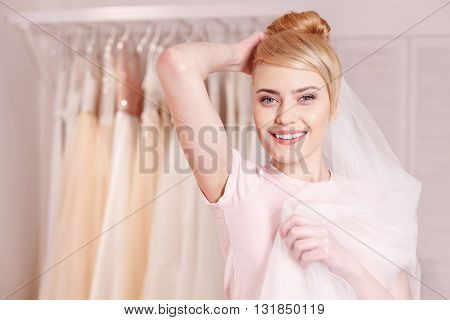 Attractive young woman is trying on wedding attire in salon. She is touching veil to her head and smiling. The lady is standing and looking at camera with joy