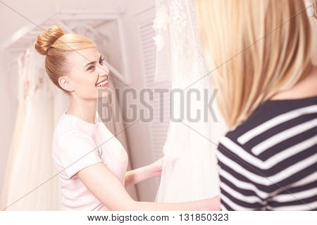 Cheerful young woman is choosing wedding dress in boutique. She is looking at the shop assistant and smiling