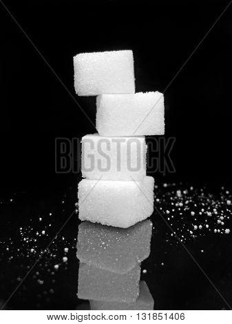 Sugar cubes on black background. Low key close-up. Stack rock.