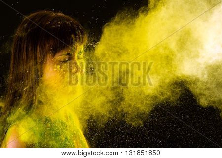 beautiful brunette girl in colors Holi on a black background