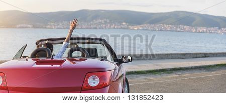 Panoramic photo of relaxing woman on the beach in the car without a roof. Vacation holiday journey to the sea or the resort.