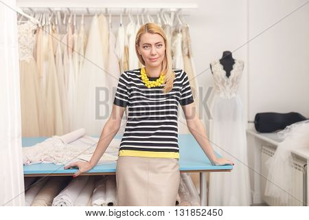 Cheerful fashion designer is working in atelier. She is standing and leaning on the table with white cloth. The lady is smiling. Elegant wedding dresses are hanging on background