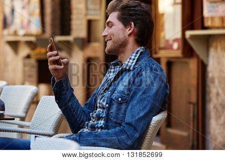 Young man with smartphone smiling in an cafe outdoor sitting