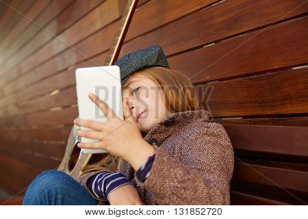 blond kid girl taking selfie with guitar and winter beret and coat on wooden background