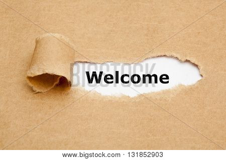 The word Welcome appearing behind torn brown paper.