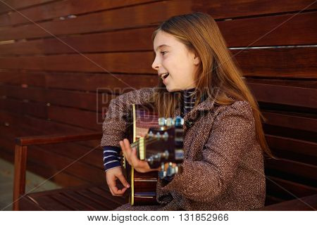 blond kid girl playing guitar with winter coat on wooden background
