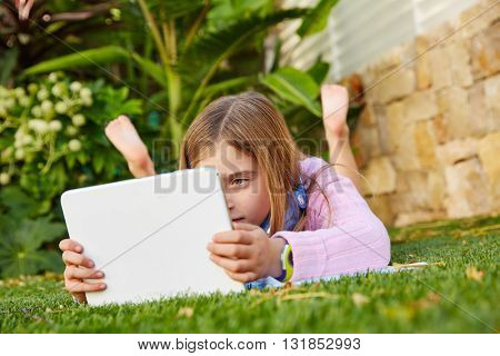 Blond kid girl with tablet pc lying on grass turf barefoot