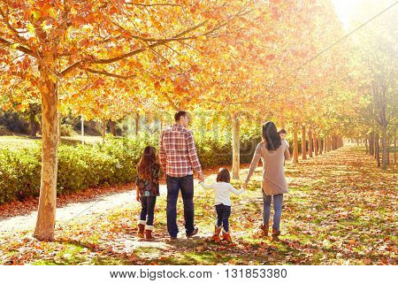 family walking in an autumn park with fallen fall leaves