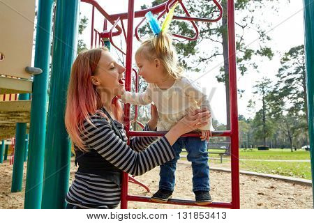 Kid girl and mother playing with playground ladder in the park