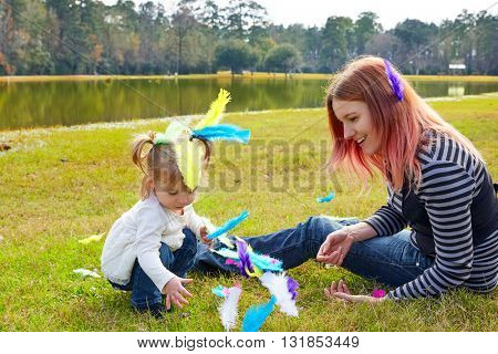 Mother and daughter playing with color feathers in a park lake