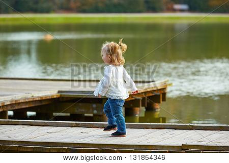 Blond Kid girl walking in the lake pier at the park