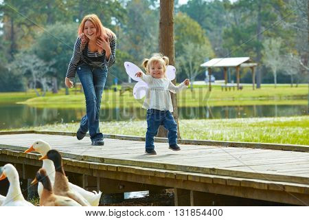 Kid girl and mother playing with ducks in the park lake