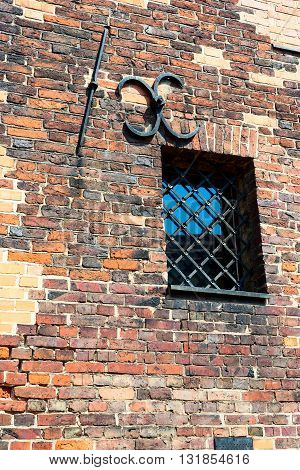 Small barred window in an old brick wall. The metal bars of the window in the form of an arch