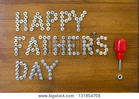 Happy Fathers Day words with screws and screwdriver on a rustic wood background
