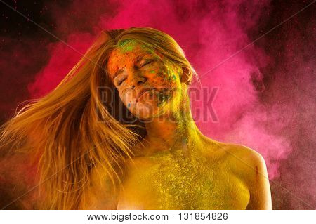 attractive blond with flying hair in the colors Holi