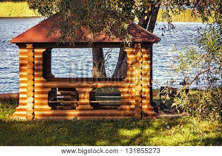 On the banks of the river in the shade of the trees is a gazebo made of logs and covered with roof tiles.