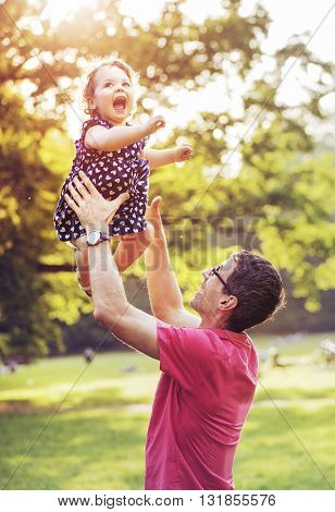 Father and his little daughter having fun in park